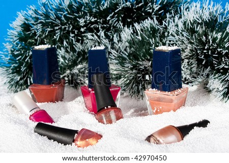 Different nail polish in to snow on a background tinsel. - stock photo