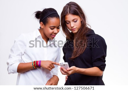 different nationalities teenage girls, caucasian woman and african american woman holds mobile phones
