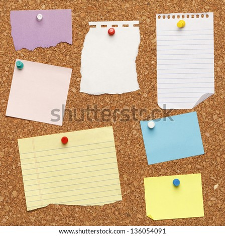 Different papers tacked on cork board. - stock photo