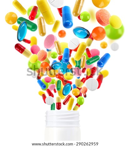 Different pills flying away from open plastic bottle isolated on white - stock photo