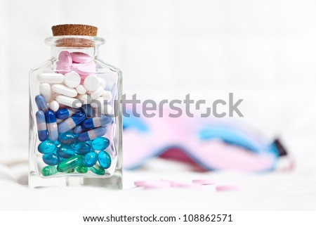 Different pills in a glass bottle and sleeping mask on the background - stock photo