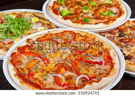 different pizza at the table - stock photo