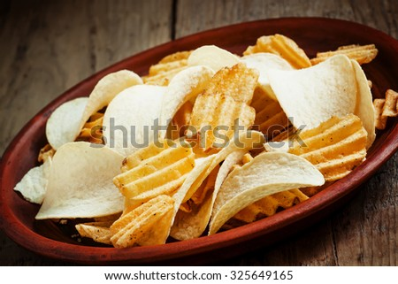 Different potato chips on a plate, beer snack, selective focus - stock photo