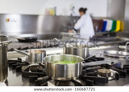 Different pots cooking on hotplate in professional kitchen - stock photo