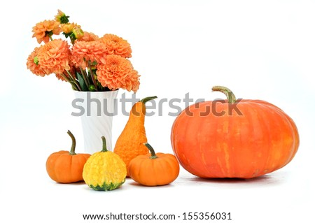 Different pumpkins with flowers in a vase