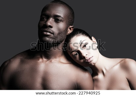Different races and one love. Portrait of shirtless African man and Caucasian woman bonding to each other while standing against grey background  - stock photo