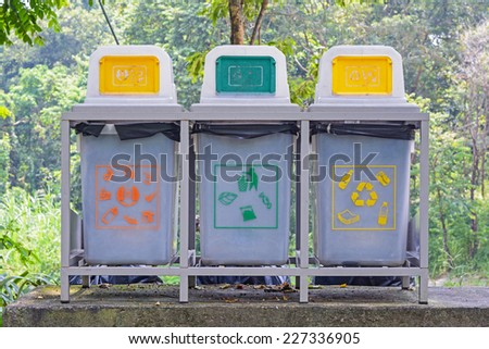 Different recycle bins on stand near footpath in the Park. - stock photo
