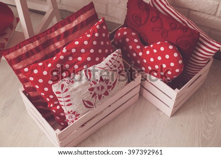 Different red and white pillows in boxes on the floor.