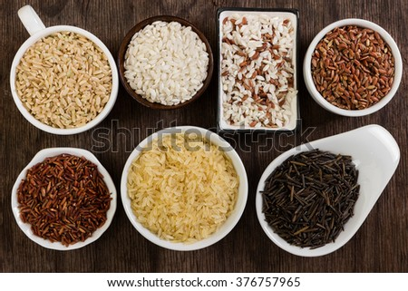Different rice in bowls on wooden background - stock photo