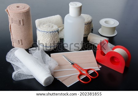 Different rolls of medical bandages and care equipment on a black background - stock photo