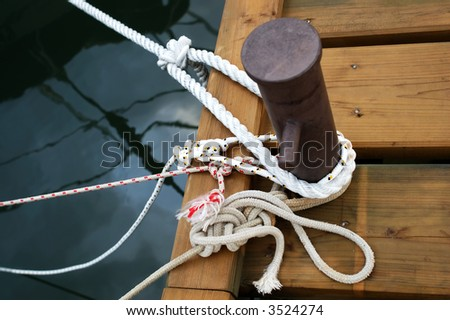 Different ropes tied to a cleat on dock - stock photo