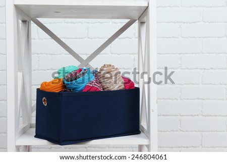 Different scarves in textile box on shelf and white brick wall background - stock photo
