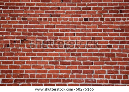 Different shades of ready and a changing pattern red brick wall - stock photo