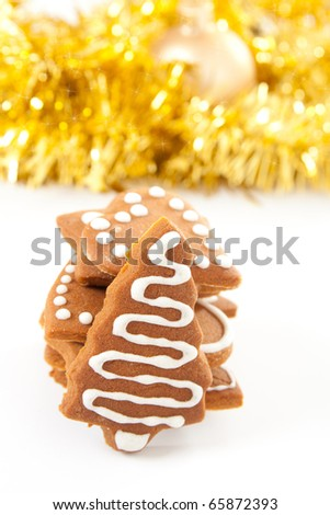 Different shaped homemade Christmas gingerbread cookies with icing and golden ribbons and bauble in background.
