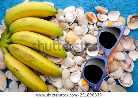 Different shells and bananas with sunglasses - stock photo