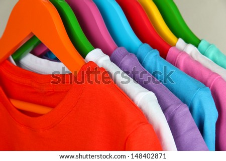 Different shirts on colorful hangers on grey background