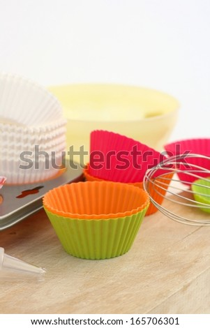 Different silicon and paper cupcake or muffin liners with a muffin pan, bowl and wire whisk - stock photo