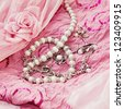 Different silver pear jewellery and closeup pearl on pink silk dress - stock photo