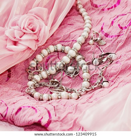 Different silver pear jewellery and closeup pearl on pink silk dress