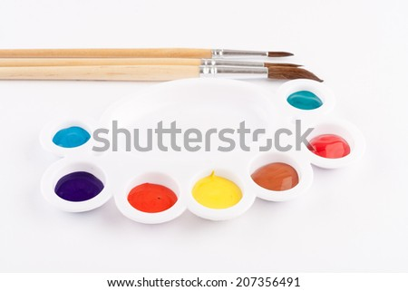 different size paint brushes and color palette - stock photo
