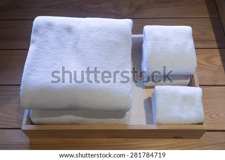 Different sizes of folded white towels in a wooden tray. - stock photo