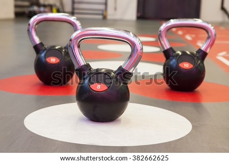 Different sizes of kettlebells weights lying on gym floor. Equipment commonly used for crossfit training at fitness club - stock photo