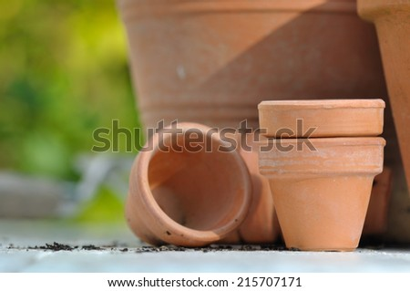 different sizes of terracotta pots on outdoor table - stock photo