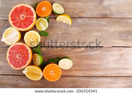Different sliced juicy citrus fruits on wooden table - stock photo