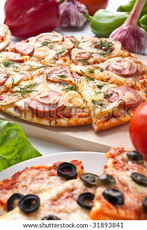 different sliced pizzas with ingredients - stock photo