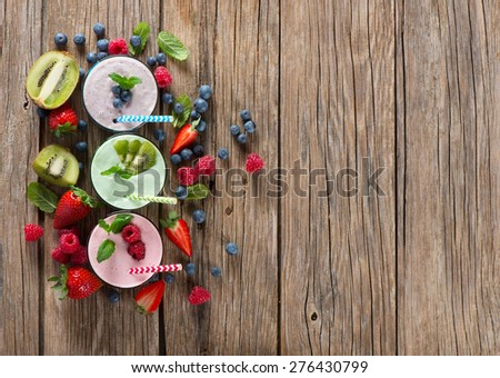 Different smoothies of berry on a wooden old background with space for text, top view - stock photo