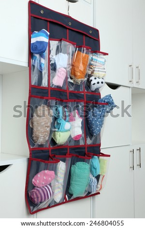 Different socks in hanging bag on closet background - stock photo