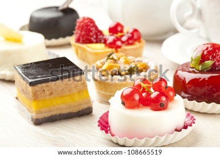 Different sort of beautiful pastry, small colorful sweet cakes - stock photo