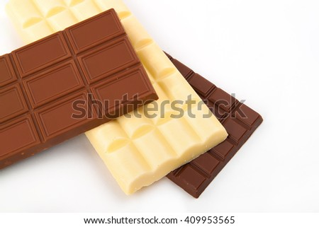 different sorts of chocolate in a stack on white background - stock photo