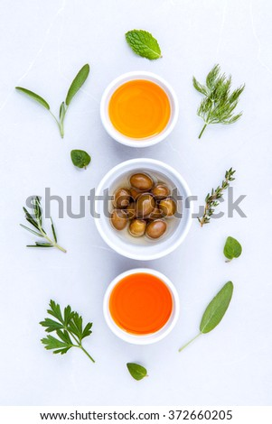 Different sorts of cooking oil,olive oil flavored and Sesame oil with spices  rosemary ,thyme,dill,sage mint and parsley set up with marble background . - stock photo
