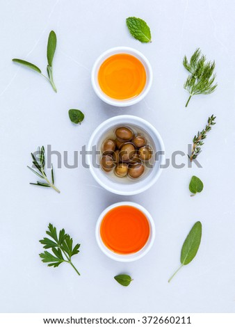 Different sorts of cooking oil,olive oil flavored and Sesame oil with spices  rosemary ,thyme,dill,sage mint and parsley set up with marble background. - stock photo