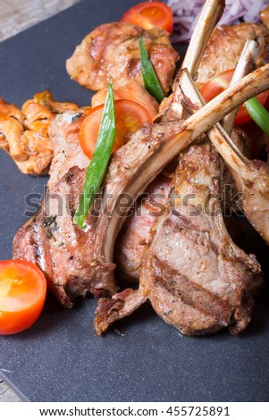 Different sorts of grilled meat served with vegetables