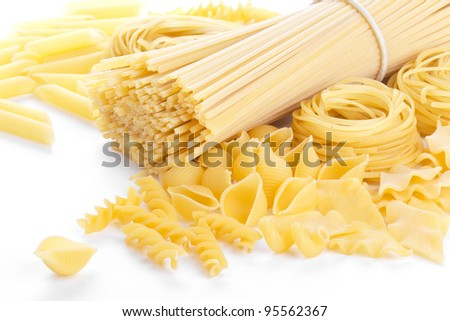 Different sorts of macaroni, closeup on white background - stock photo