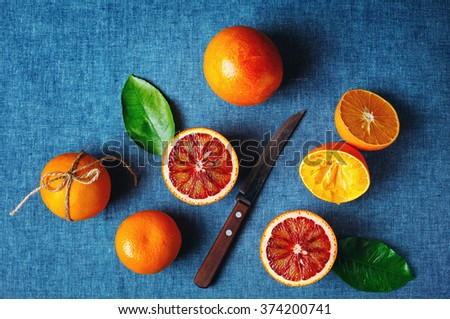 Different Sorts of Ripe Juicy Orange Fruits on Blue Textile background. Vibrant Colors, Great Contrast. Top View. - stock photo