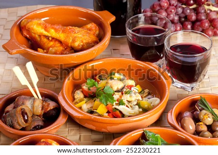 Different spanish appetizers, tapas including dates in bacon, seafood salad, chicken in tomato sauce and pickled olives, red wine and grapes. - stock photo