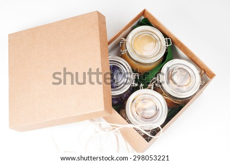 Different spices in jars and paper box with opened lid - stock photo