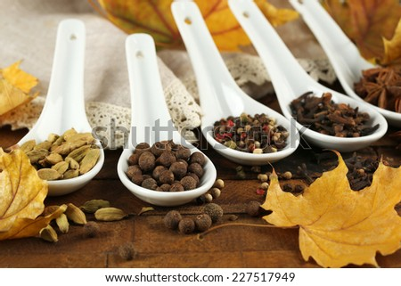Different spices in spoons with yellow leaves on wooden background