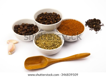 Different spices in white dishes on white background