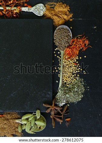 different spices on a black background (paprika, turmeric, pepper, aniseed, cinnamon, saffron) - stock photo