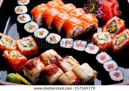 Different sushi rolls on a black plate. - stock photo