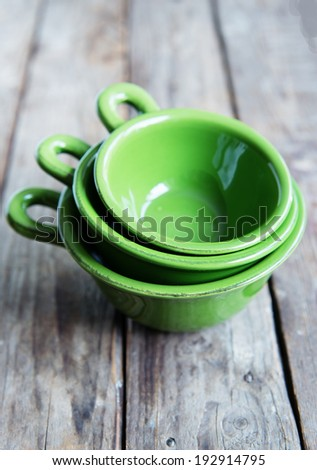Different tableware on old, wooden rustic table, green kitchen bowls - stock photo