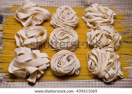 Different tagliatelle homemade portions dry on long yellow spaghetti italian pasta on wooden background - stock photo