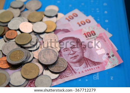 different THB coins and THB banknotes on the background of blue keyboard,select focus.