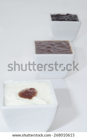different tipes of jam in white bowls on white background - stock photo