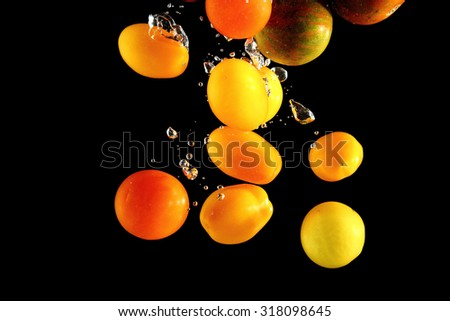 Different tomato cultivars falling into water at black background - stock photo