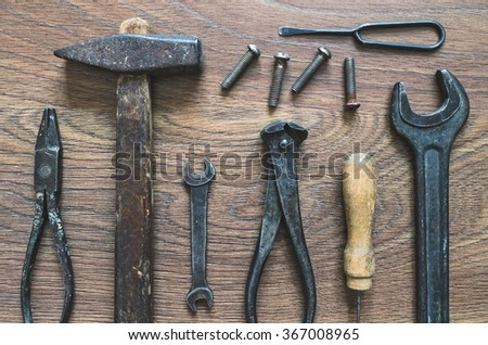 Different tools (pliers, hammer, awl, wrench, nippers, chisel) on a wooden background. - stock photo